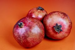 three pomegranate on red orange background royalty free stock images