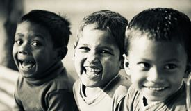 Three poor kids smiling together. The three poor children smiling together sitting in a place unique black and white editorial photo royalty free stock photos