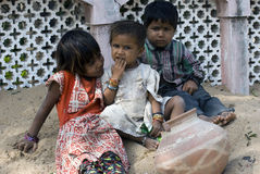 Three poor slum children playing on sand Stock Images