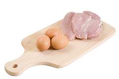 Three pork steaks and brown eggs on cutting board Stock Images