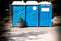 Three portable blue WC toilet cabins at construction site