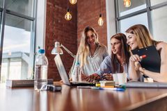 Three positive businesswomen working on laptop discussing joint business project.  royalty free stock photos