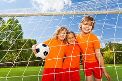Three positive girls in uniforms with football. Standing behind the white net of woodwork and smile Royalty Free Stock Image