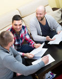 Three positive males with documents Royalty Free Stock Images