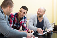 Three positive males with documents Stock Photography
