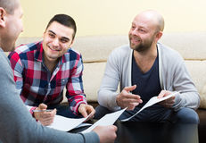 Three positive males with documents Royalty Free Stock Photography