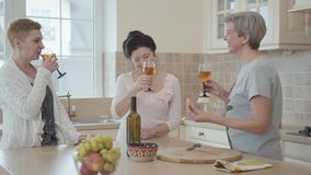 Three positive mature women communicating at home near modern table in the kitchen. One lady says a toast and they clink. Glasses. Senior ladies having fun stock footage