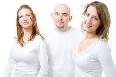 Three positive people in white. Three positive people - two women and one man in white,isolated Royalty Free Stock Image