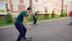 Three positive teenage friends with skateboards riding in the street. Young people sliding ahead doing tricks and stock video