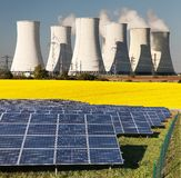 Three possibility for production of electric energy. Nuclear power plant with golden glowering field of rapeseed and photovoltaic sunny power plant - Three Royalty Free Stock Image