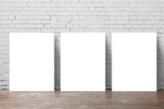 Three  poster. Standing next to a brick wall Stock Image