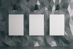 Three posters in dark room. Three blank posters in room with dark polygon patterned wall and ceiling lamps. Mock up, 3D Rendering Royalty Free Stock Photography