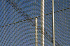 Three posts of fencing. Three fence posts are silhouetted against a blue sky Royalty Free Stock Image