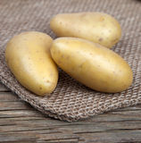 Three potatoes lying on a bag Stock Images