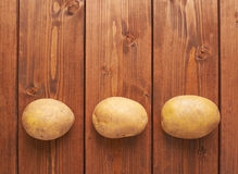 Three potatoes over the wooden surface Stock Images