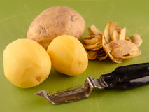 Three potatoes with peeler on used green board. One unpeeled and two peeled potatoes on used green plastic board with peeler, simple food preparation Royalty Free Stock Photo