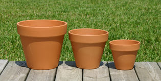 Three Pots are We. 3 terracotta pots different sizes on wooden deck with grass background stock photos