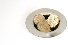 Three Pound Coins Money Down the Drain. Three british pound coins stuck in a drain plughole of a batch or sink Royalty Free Stock Image
