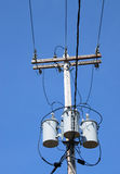 Three electric power transformers wires blue sky Stock Image