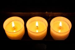 Three prayer candles. In a row in the church Royalty Free Stock Photo