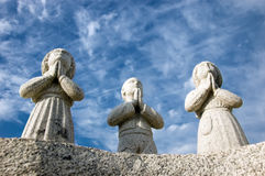 Three praying statues. Three praying stone statues or saints stock image