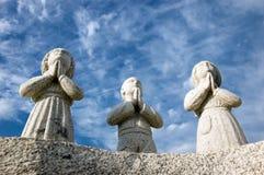 Three praying statues Stock Image