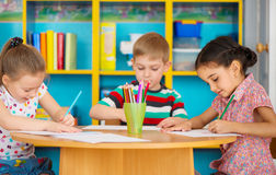 Three preschool children drawing at daycare Stock Image