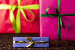 Three presents, bows and ribbons. The golden bow and blue wrapping of a small gift box are in focus and do contrast with the red and magenta color-fields of two Stock Photos
