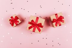 Three presents with red bow on pink stock photography