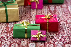 Three Presents Standing Out. Single-colored gifts in magenta, green, red and gold placed on a festive cloth. Plenty of text space. Background for many gift Royalty Free Stock Photography