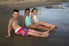 Three preteen children sitting on the beach in the water smiling Royalty Free Stock Photos
