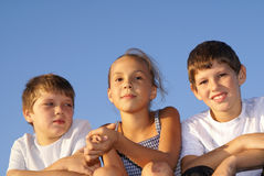 Three preteen friends. Enjoying summer outdoors on blue sky background Royalty Free Stock Images