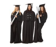 Three pretty female graduates smiling happy. Three pretty female graduates in academic dress smiling happy, holding diploma Royalty Free Stock Photos