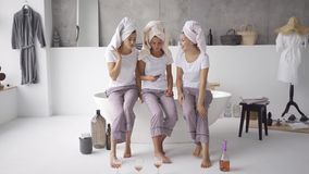 Three pretty girlfriends in the same pajamas and towels on heads spending time together at home looking on the cellphone. Three positive girlfriends in the same stock footage
