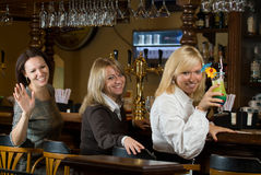 Three pretty girls at a bar counter Stock Photography
