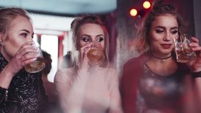 Three pretty girls having a conversation, laughing and drinking alcohol. Awaited meeting. Celebrating, having a party. Bar settings, true friendship. Close up stock footage