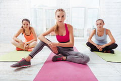 Three pretty girls posing in a fitness studio Royalty Free Stock Image