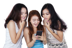 Three pretty girls reading message together Royalty Free Stock Image