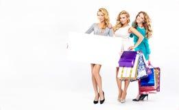 Three pretty ladies on the seasonal sales royalty free stock images