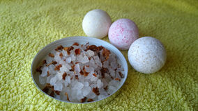 Three pretty little bombs for the bath and large bath salt with flower petals on the towel Stock Photo