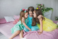 Three pretty little girls sit on a bed and hug each other Royalty Free Stock Photo