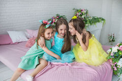 Three pretty little girls sit on a bed and smile Stock Photo