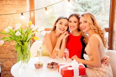 Three pretty, nice, confident, successful girls sitting in restaurant, embracing, having glasses with champagne, wine, alcohol, b royalty free stock photography