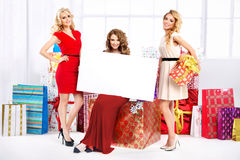 Three pretty women with empty board Royalty Free Stock Photography