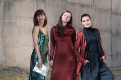 Three pretty women Fashion street style smiling stock images