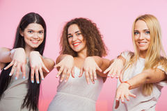 Three pretty women show hands fingers and nails. Manicure concept. Blonde curly brown and long dark hair royalty free stock images