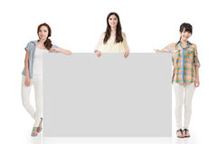 Three pretty women showing an empty board. With copyspace for advertising Royalty Free Stock Photography