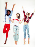 Three pretty young diverse nations teenage girl friends jumping happy smiling on white background, lifestyle people. Concept close up Royalty Free Stock Image