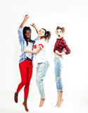 Three pretty young diverse nations teenage girl friends jumping happy smiling on white background, lifestyle people. Concept close up Royalty Free Stock Images