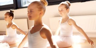 Three pretty young girls in ballet class. Sitting on the floor in a graceful pose in the white tutus in the warm sunshine royalty free stock photos